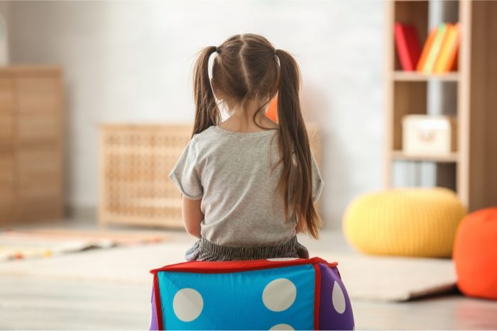 girl with autism sitting on a block in playroom
