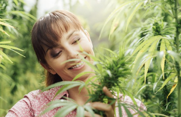 woman smiling at cannabis plants