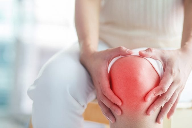 Woman Clutching Arthritic, Inflamed Knee