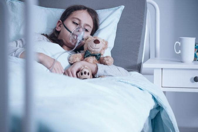 Cystic fibrosis child laying in hospital bed on oxygen