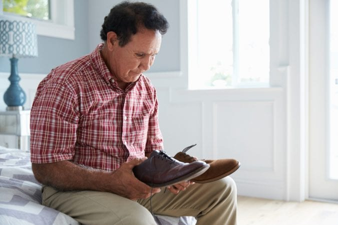 Dementia patient man sitting on side of bed staring at shoes in his hands