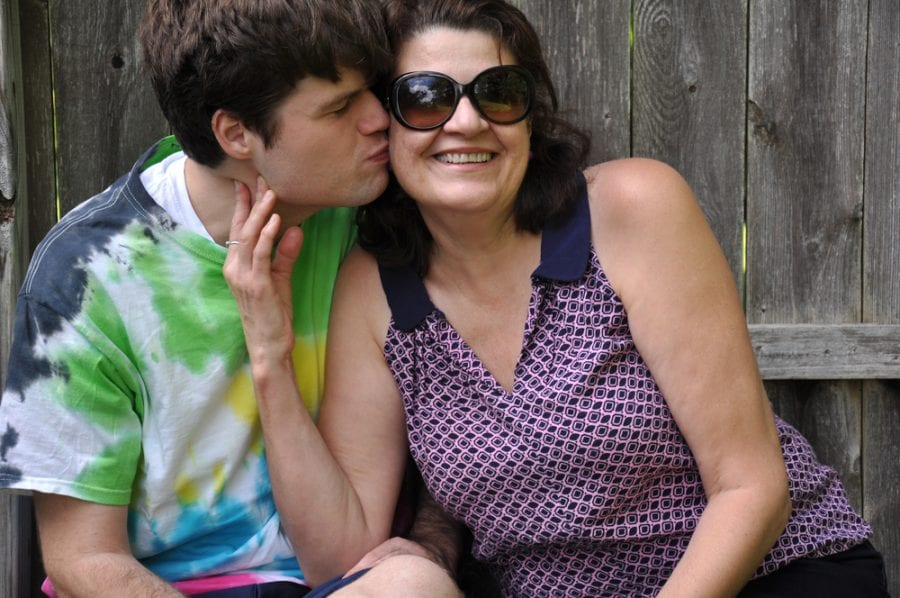 Teenage Autistic Boy Kissing His Smiling Mother