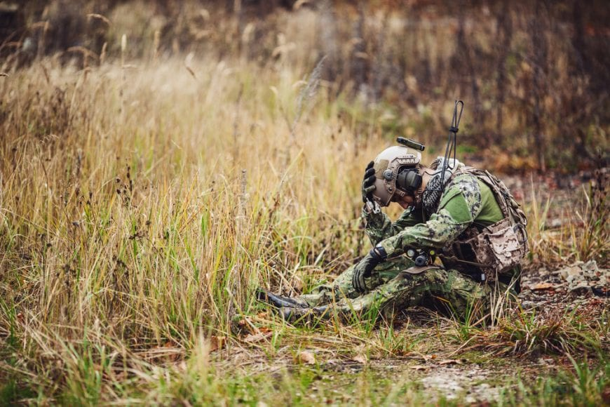 ptsd and pain for this Soldier sitting in field clutching his head, who may be suicidal