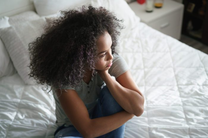 anxiety and cannabis represented by young black female looking worried on bed