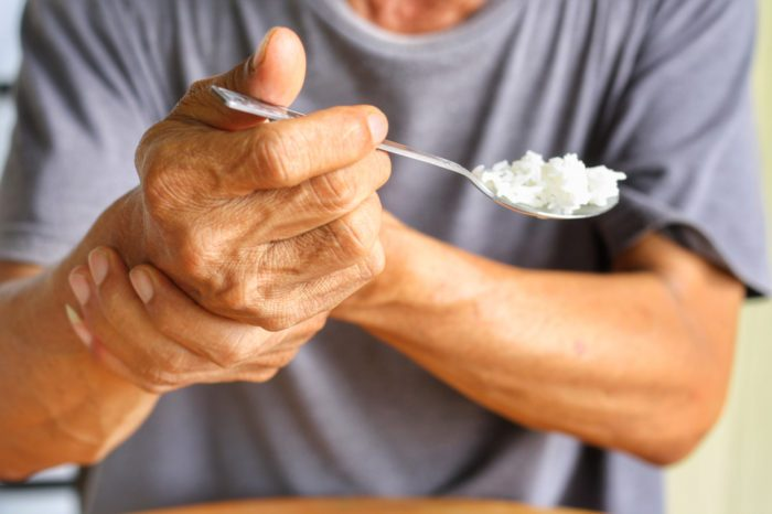 white man struggling to eat by holding shaking wrist representing cbd and parkinsons