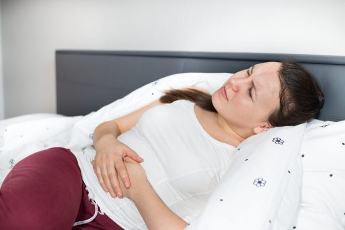 Young woman clutching her gut rom abdominal pain