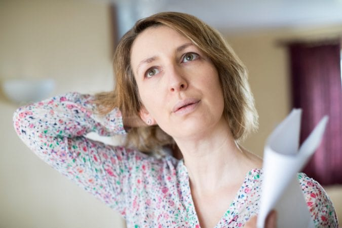 Middle Aged Woman Sweating and fanning with paper