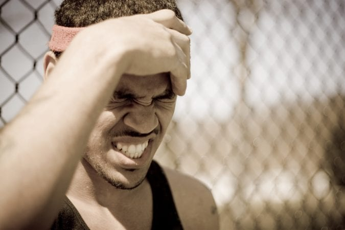 Young Athlete Clutching Head and Grimacing