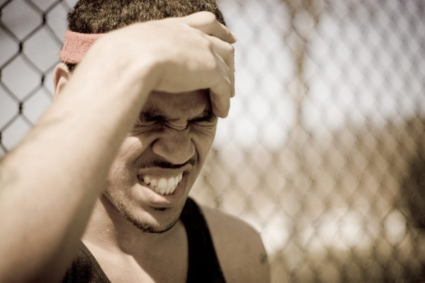 Young Athlete Clutching Head and Grimacing at injured brain