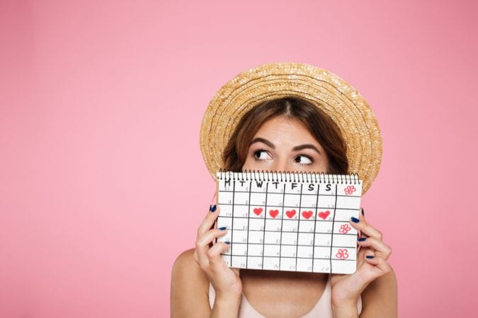 Woman Holding up Calendar with Menstruation Days Marked Off