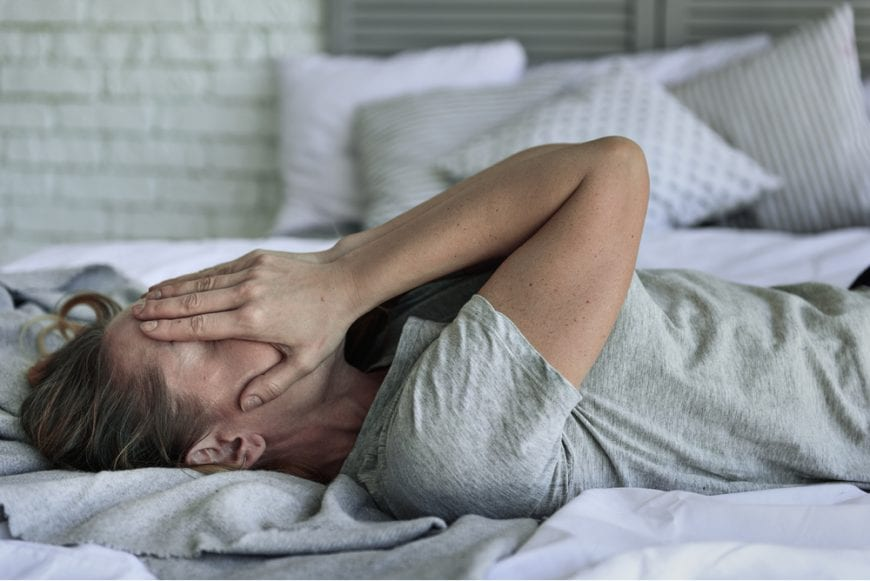 Woman Lying in Bed with hands over face