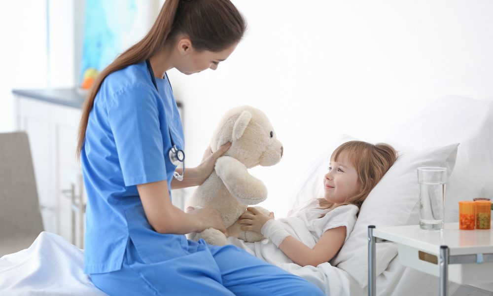 tic disorders represented by child in hospital bed and nurse playing with her
