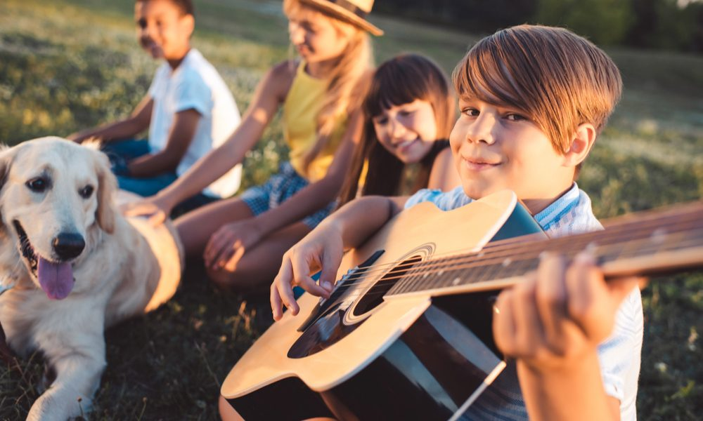 tic disorders represented by child playing guitar and smiling into camera