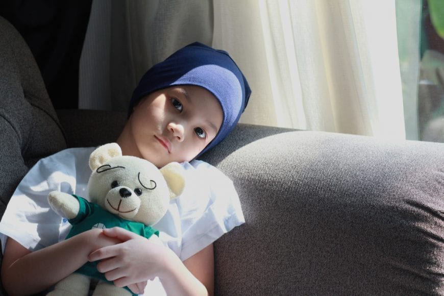 Child laying in bed with cancer