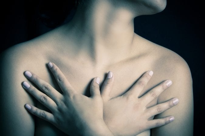 Black and white image of woman covering breasts with her hands