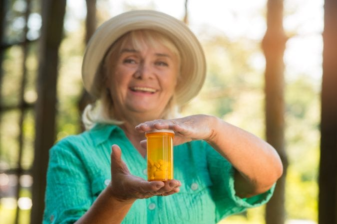 Senior woman holding out a vial of pills