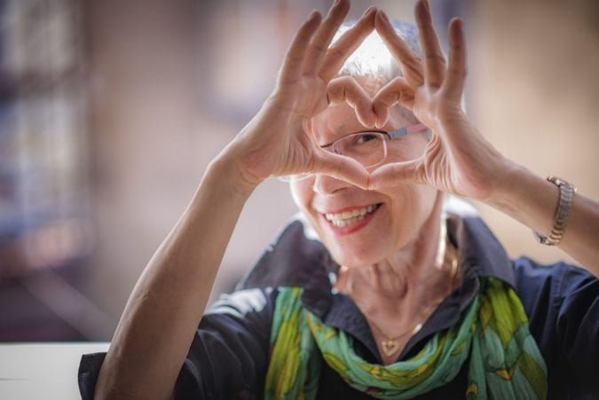 Elder woman smiling and making heart shape with her hand