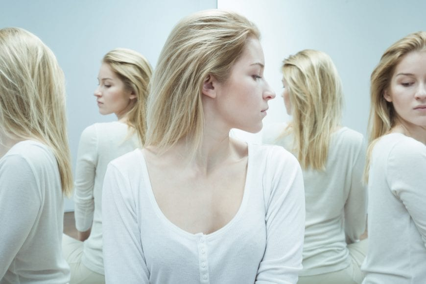 Woman with schizophrenia looking in a carnival mirror that multiplies her image