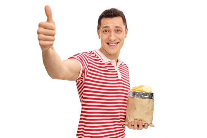 Happy guy with chips giving the thumbs up