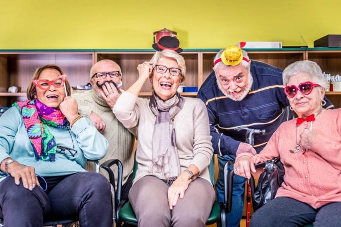 Seniors in care facility dressed up and laughing