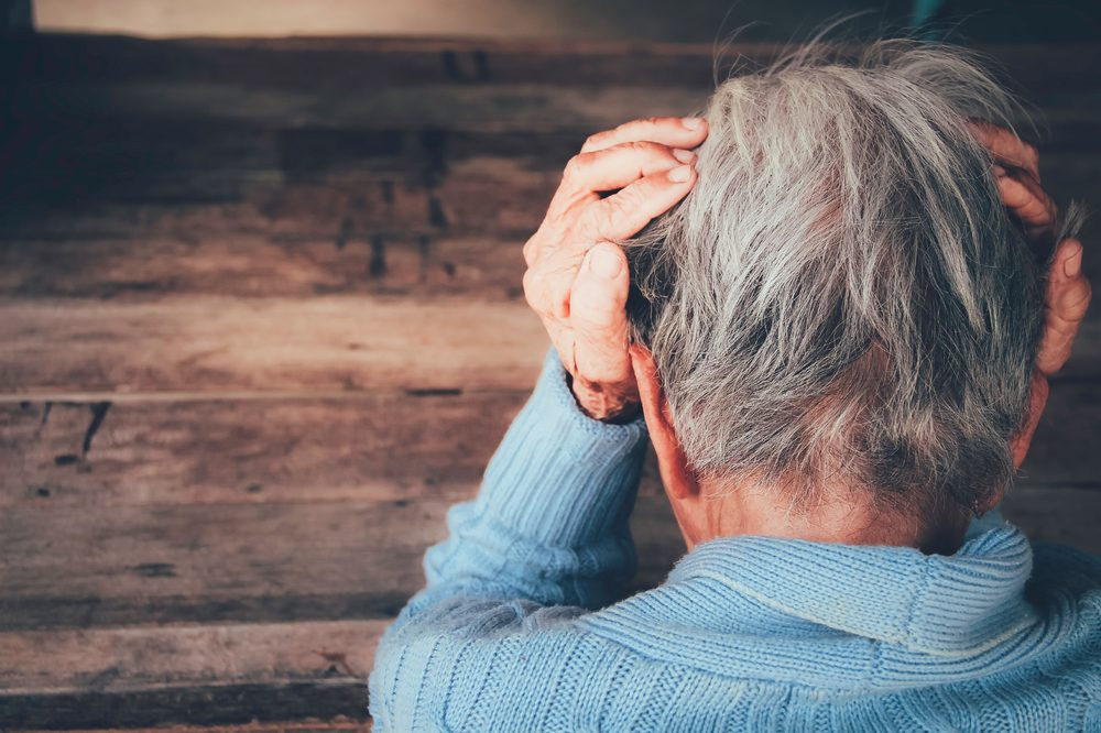 elder woman holding her head and sad to represent THC in cannabis for dementia