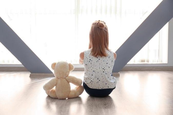 ASD Girl sitting with her teddy bear