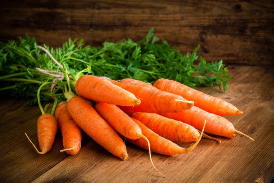 Bunch of Carrots on wooden floor close up