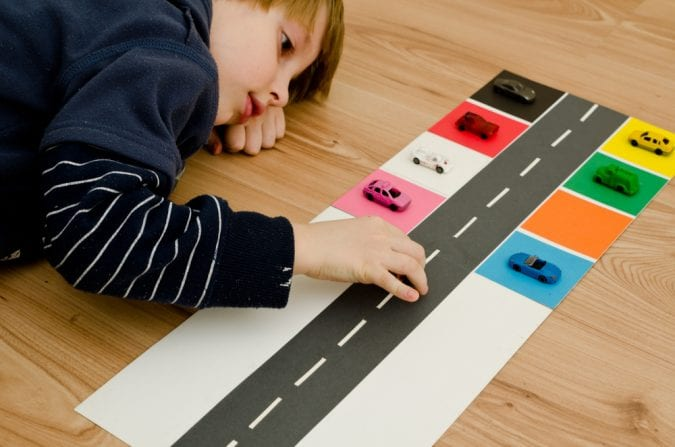 Boy with autism playing with cars on the floor