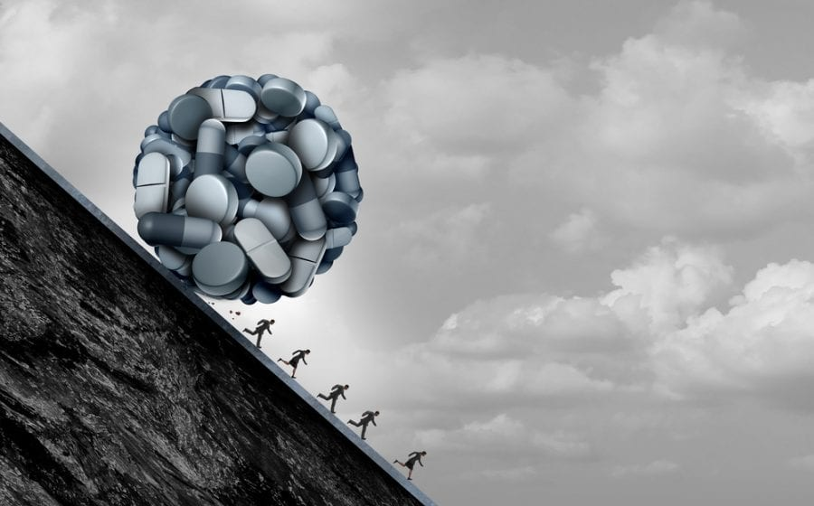 Ball of opioids rolling down a hill over people