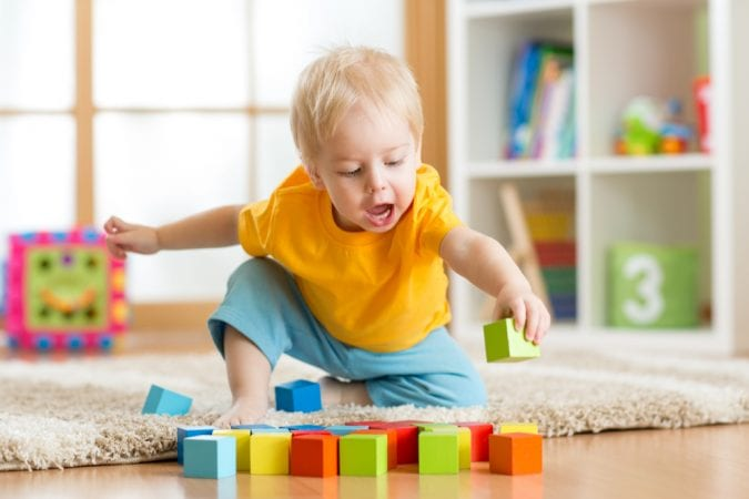 Toddler playing with blocks on the floor