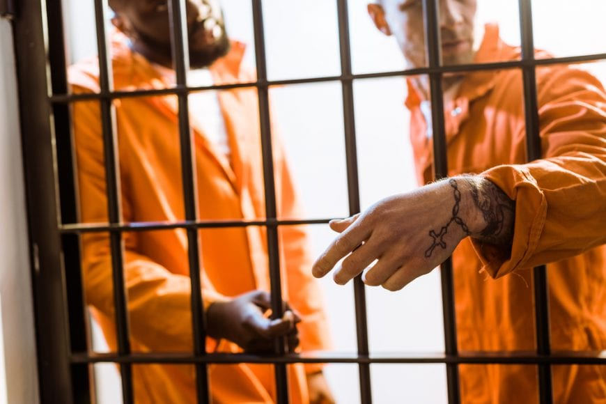 American justice system represented by two men in jail cell