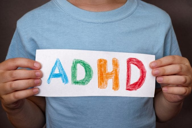 man holding sign that says ADHD