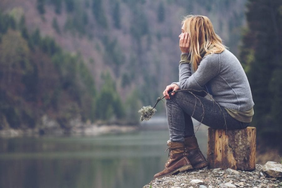 Woman sitting on a tree stump at edge of river with no human connection