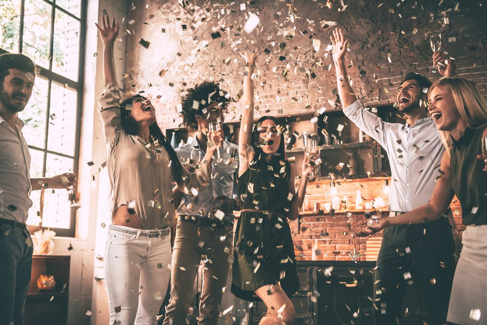 Friends celebrating with confetti toss in kitchen
