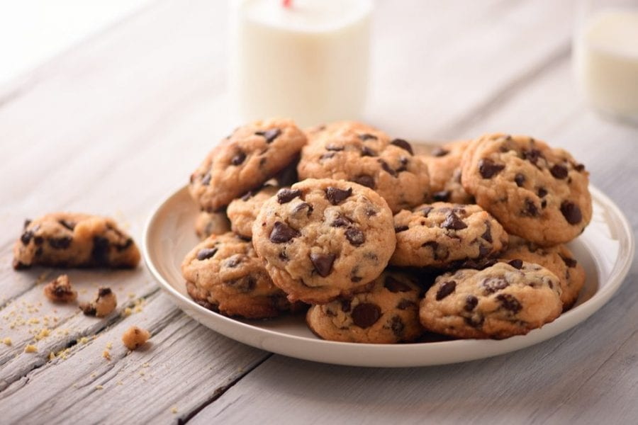 Plate of chocolate chip cookies with milk in background