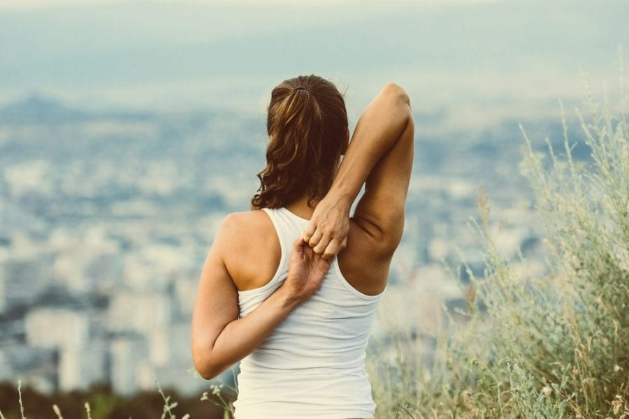 young woman using best cannabis for pain and able to do yoga