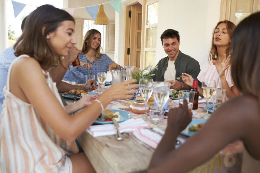 friends eating dinner together and laughing over cannabis salad