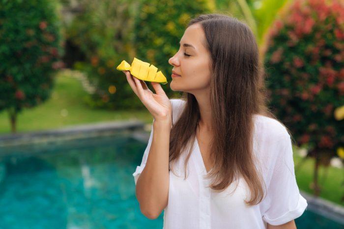 woman happily eating mango