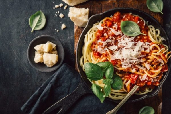 pasta with bolognese in a frying pan topped with basil