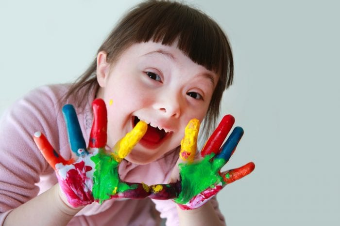Happy child with Trisomy 21 holding up painted hands