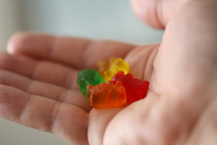 Hand holding out CBD Gummy Bear