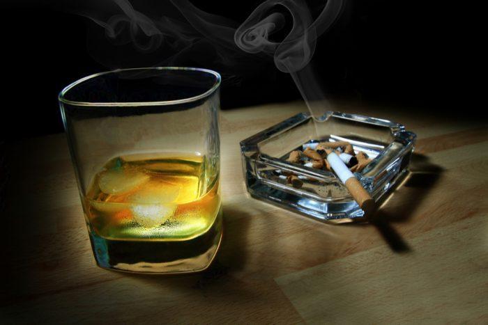 scotch beside ashtray with smoking cigarette