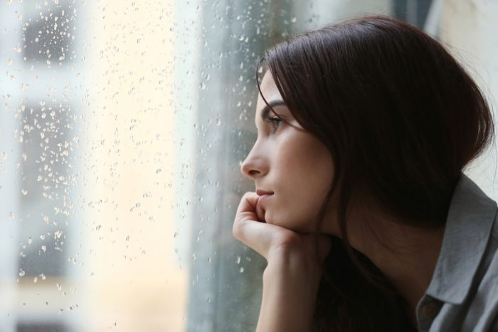 depressed girl looking out rainy window