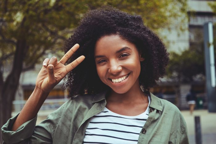 smart looking girl giving peace sign