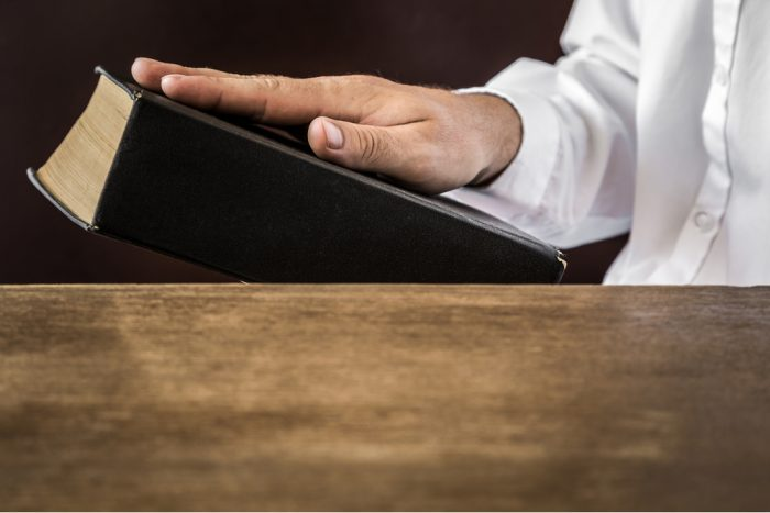 hippocratic oath of do no harm represented by doctor with hand on book