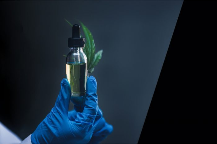 dissolvable thc in a dropper held by a gloved hand with a leaf as well