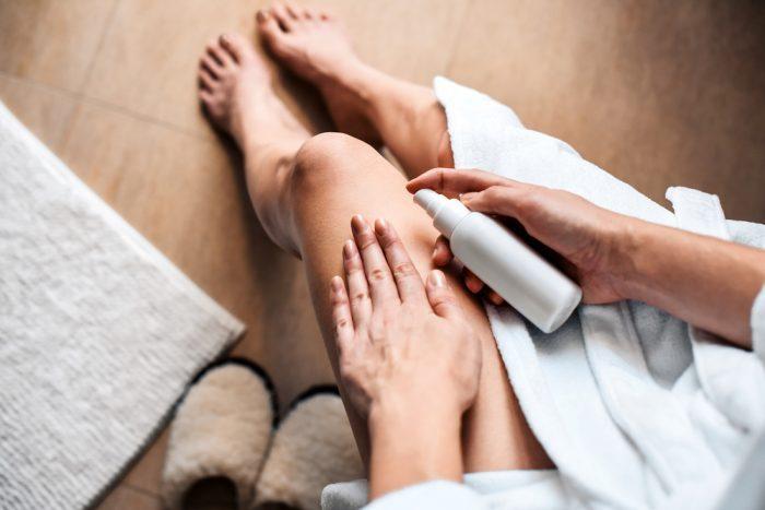 cannabis for MS woman spraying cannabis cream on legs