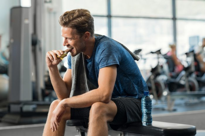 man eating a bar in a gym