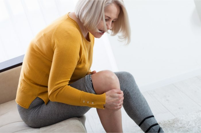 chronic non cancer pain represented by woman holding her knee