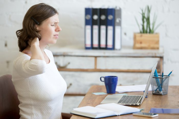 chronic non cancer pain represented by young woman at desk rubbing neck